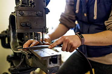 Female saddler standing in workshop, sewing leather strap on saddlery sewing machine, Berkshire, United Kingdom