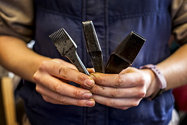 Close up of person holding three metal saddle making tools, Berkshire, United Kingdom