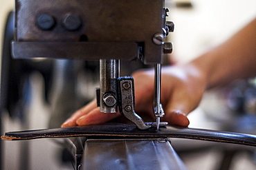 Close up of person sewing piece of leather to make a saddle, Berkshire, United Kingdom