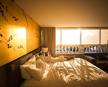 Adult woman executive lying on hotel bed in early morning sunlight, looking at smart phone, United States