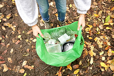 Plastic bag being held open filled with plastic litter, Bristol, United Kingdom