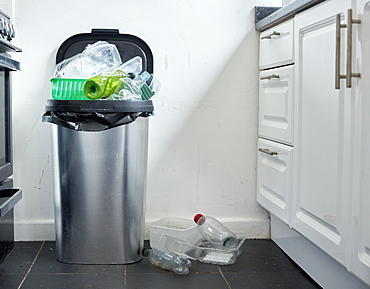 Various used plastic containers overflowing from dustin in kitchen, Bristol, United Kingdom