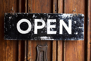 Close up of black and white open sign on wooden door of a cafe