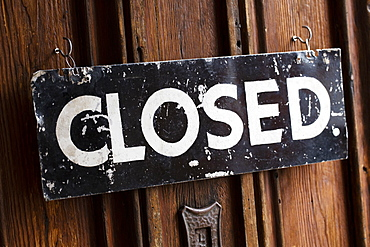 Close up of black and white closed sign on wooden door of a cafe