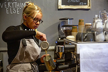 Blond woman wearing glasses and apron standing at espresso machine in a cafe, pouring milk into metal jug