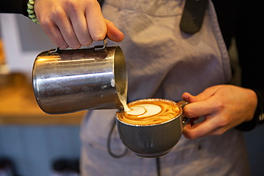 High angle close up of barista pouring milk foam onto cappuccino in a cup