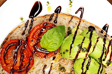 High angle close up of tomato and avocado bruschetta with balsamic vinegar reduction on a plate