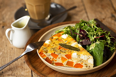 High angle close up of frittata with a with baby leaf salad in a cafe