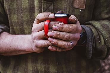 Close up of man with dirty hands holding red enamel mug, Devon, United Kingdom
