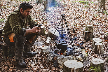 Man sitting by a camp fire in a forest, boiling kettle of water, Devon, United Kingdom