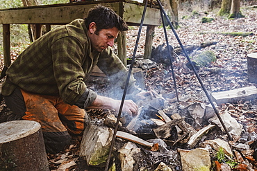 Man starting a camp fire in a forest, Devon, United Kingdom