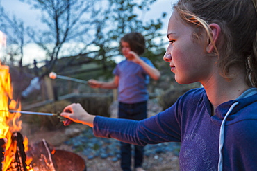 A teenage girl making smores with her brother over a fire in a garden at dusk