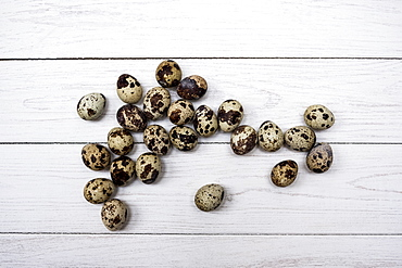 High angle close up of quail eggs on white wooden table