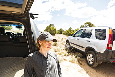 14 year old girl resting on SUV, Galisteo Basin, New Mexico, United States of America