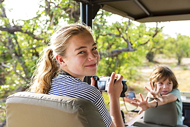 Two children, a teenage girl and young boy in a jeep in a game reserve, Moremi Game Reserve, Botswana