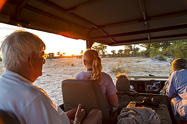 Three generations of a family on safari, in a jeep out at sunset, Moremi Game Reserve, Botswana
