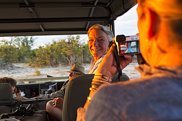 Senior woman in a jeep turning and smiling for the camera, Moremi Game Reserve, Botswana