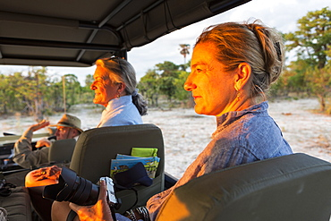 Senior woman and mature daughter, two generations of women in a safari jeep looking out at sunset, Moremi Game Reserve, Botswana