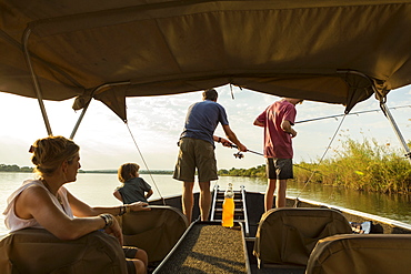 A group of tourists, family fishing from a boat on the Zambezi River, Botswana, Zambezi River, Botswana