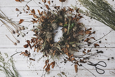A wreath made from twigs and dried leaves, teasels and seedheads,