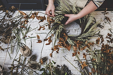 Woman making a small winter wreath of dried plants, brown leaves and twigs, and seedheads