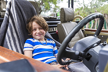Smiling Six year old boy in the driver's seat of a safari vehicle in Botswana