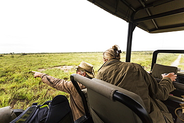 Adult woman and a safari guide leaning out looking across a plain to animals in the distance