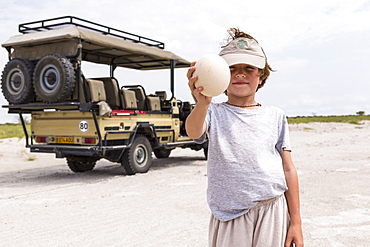 Boy holding up a large ostrich egg