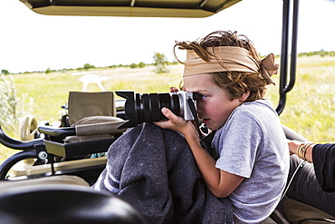 Six year old boy taking pictures from safari vehicle, Botswana