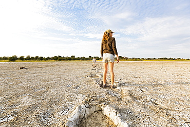 Thirteen year old girl leaping into elephant footprints, Nxai Pan, Botswana