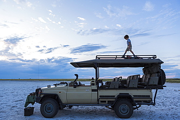 Six year old boy and older sister standing on top of safari vehicle, Nxai Pan, Botswana