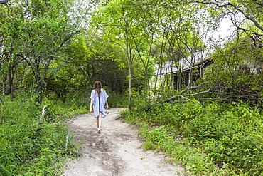 Thirteen year old girl walking on dirt path to tented camp, Maun, Botswana