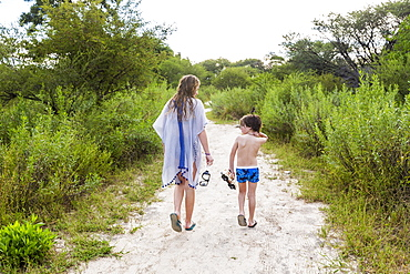 rear view of teen sister and her brother walking on dirt path, Maun, Botswana