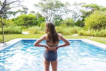 rear view of teen girl looking at pool, Maun, Botswana