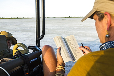 A woman looking at a book or journal in a safari vehicle, Botswana