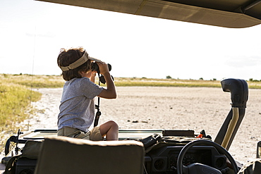A six year old boy looking through binoculars across a salt pan