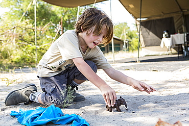 A six year old boy playing with toys in a tented camp, Nxai Pa, Botswana