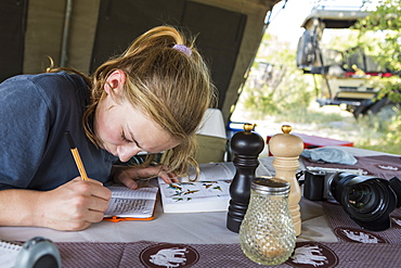 A teenage girl writing in her journal in a tent