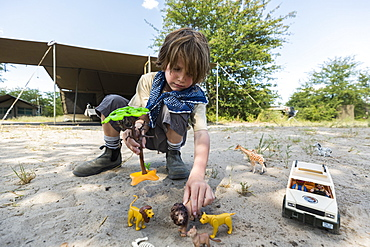 A boy setting up a safari scene with toy jeeps and wild animal toys and a tall tree