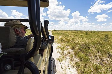 safari guide and vehicle on dirt road