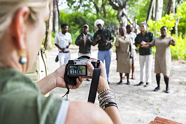 adult woman taking pictures of tented camp staff, Botswana