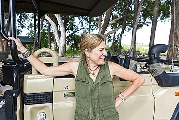 portrait of adult woman leaning on safari vehicle, tented camp, Botswana