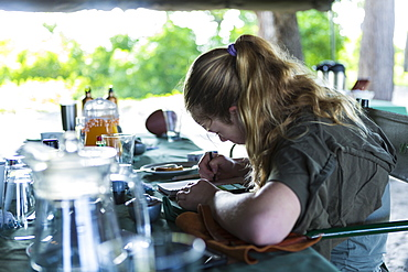 Thirteen year old girl writing in her journal, tented camp, Botswana