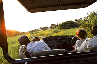 A six year old boy in the driving seat, steering safari vehicle at sunset, Botswana