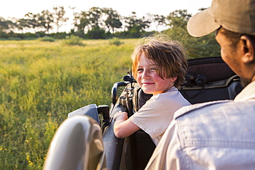 smiling Six year old boy steering safari vehicle, Botswana