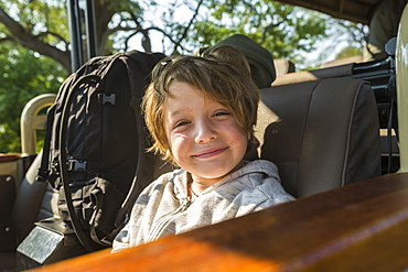 portrait of smiling Six year old boy in safari vehicle, Botswana