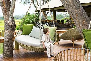 Six year old boy sitting on swing, tented camp, Botswana