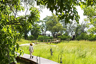 Six year old boy walking on wooden walkway in a safari camp