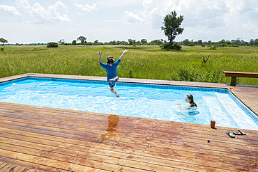 Six year old boy jumping into pool, tented camp, Botswana