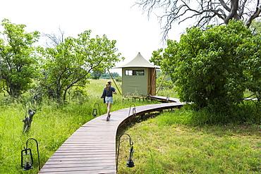 Thirteen year old girl walking wooden path, tented camp, Botswana